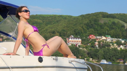 woman in bathing suit and spectacles sits on yacht shaking on waves