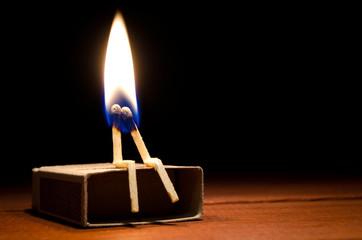 Two burning match humans sitting on matchbox on dark background