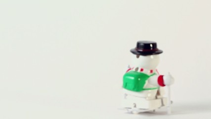 Hand wind up clockwork toy snowman on ski which ride on white