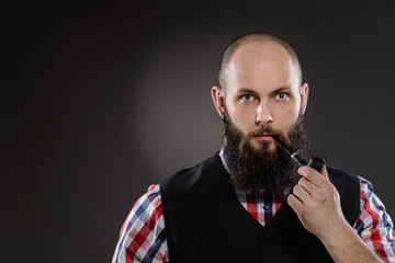 Bald bearded man in checkered shirt