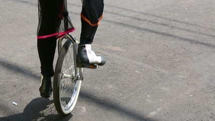 Feet of clown in shoes riding on unicycle on holiday outdoor