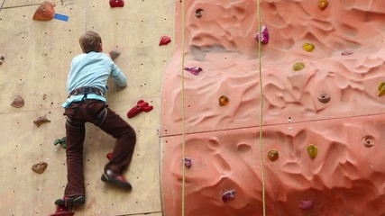 Boy-beginner climbs up on vertical rock-climbing wall