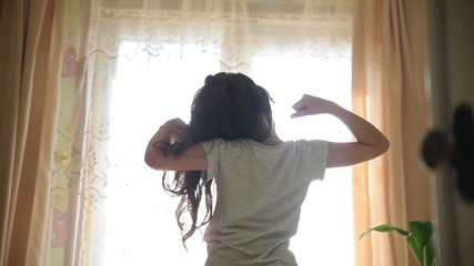 Teen girl stretches awake standing at the window silhouette spin