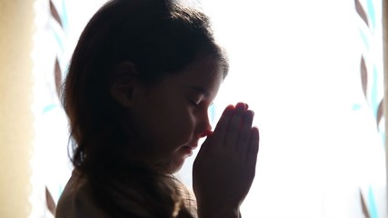 child teen girl praying prays silhouette in window video hd