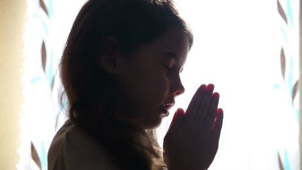 child teen girl praying prays silhouette in the window video hd