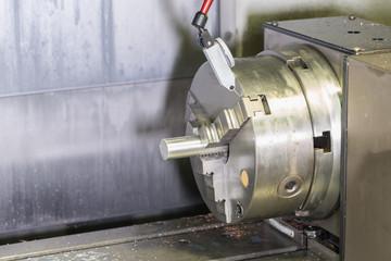 Milling detail on metal cutting cnc machine with raw metal tube