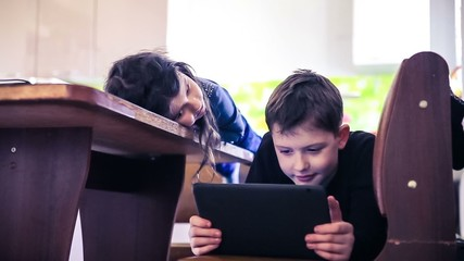 children boy and girl teens playing in the tablet online video