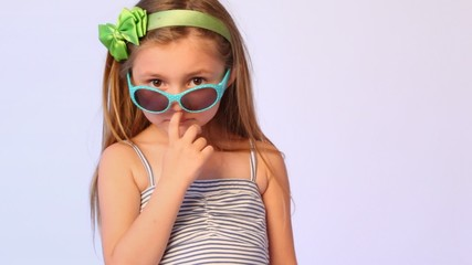girl wearing spectacles on nose pulls them finger over eyes and sticks out lips