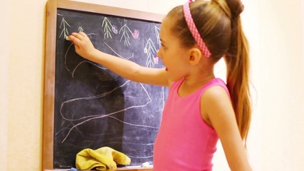 A girl in pink shirt draws trees by colored chalks on blackboard