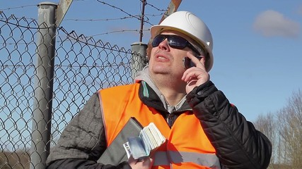 Engineer with euro banknotes talking on cell phone