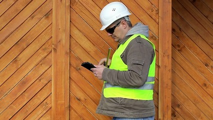 Engineer with tape measure and tablet PC near wooden building