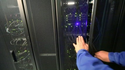 Man closes doors of server rack with many network equipment