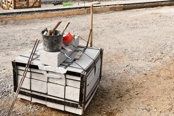 Ein Eimer mit Werkzeug auf einer Palette mit Bordsteinen