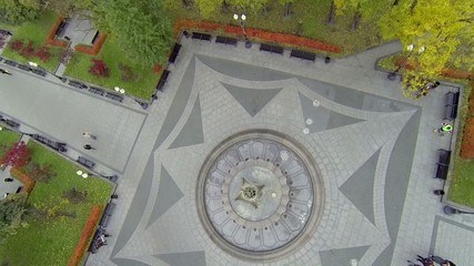 People walk by park near fountain with ornamental pavement