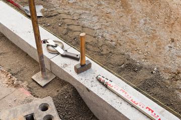 Verschiedene Werkzeuge bei der Verlegung neuer Bordsteine