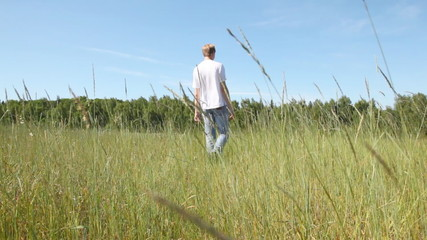guy goes across field among high grass to wood