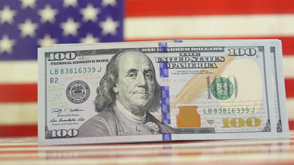 One hundred dollars bills on American flag in 4K UHD video.