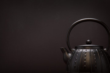 Image of traditional eastern teapot over dark background