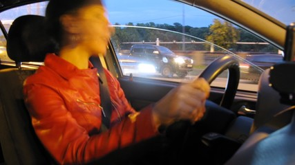 Beautiful woman goes in car in evening fastened by seat belt