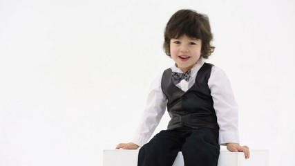 Little boy in vest and bow-tie sits and claps hands in studio