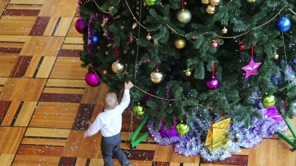 Little boy in mask run around Christmas tree with colorful balls