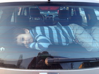 child sitting in trunk of a family car