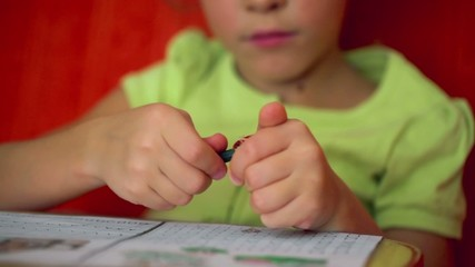 Little girl sharpens pencil above paper with shapes for draw