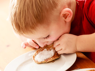 Little boy eating apple pancakes at home