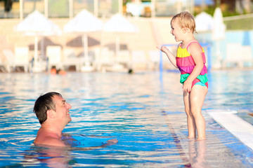Father and daughter having fun in swimming poo