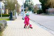 Little girl riding tricycle on the street