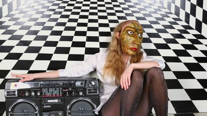 Sexy girl in mask sits near old tape cassette recorder