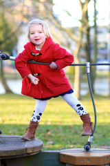 Little girl in red coat playing at the park in spring