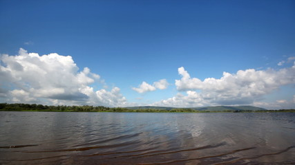 landscape river with distant coast and sky with clouds over it