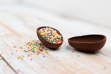 Chocolate egg with colorful sprinkles on white wooden surface