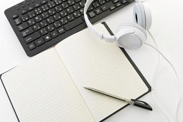 パソコンキーボードとノートとヘッドフォン