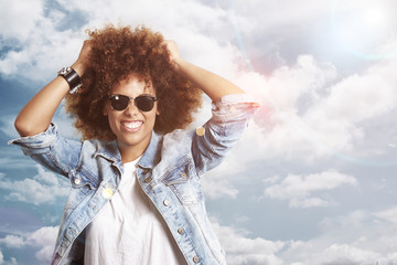 happy woman with a afro hair on a sky background