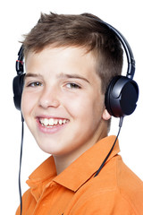 Close-up of a smiling boy with headphones listening to music, is