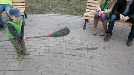 Little boy plays with broom near his parents which sit on bench