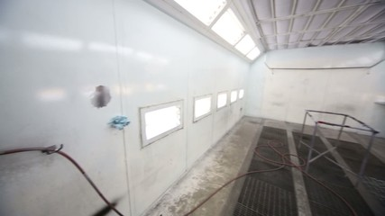 Atomizer in empty paint-spraying booth with metal walls for cars