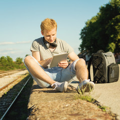 Young hipster man with tablet and headphones outdoors in summer
