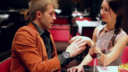Man takes hand of woman and speak during sit at restaurant