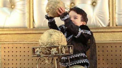 Little boy in a suit of black prince raises the golden ball