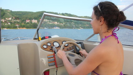 woman in bathing suit at wheel of small boat floats on river waves