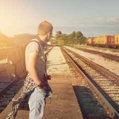 Young hipster man with backpack waiting for train