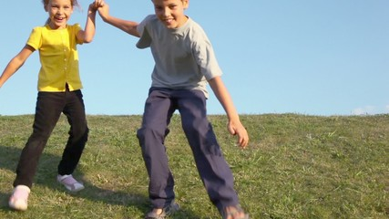 Two kids boy with little girl hold hands and run closer from behind of grass hill at sunny summer day