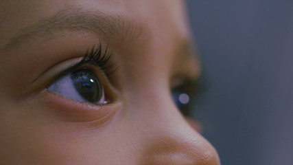 Slow motion eyes of a young girl watching a screen
