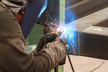 welder is welding steel pipe with all safety equipment