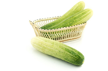 Long cucumber in small basket isolated on white background