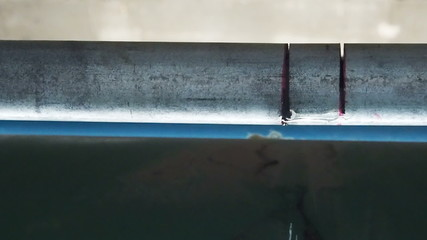 Close up water leak drop from steel pipe.