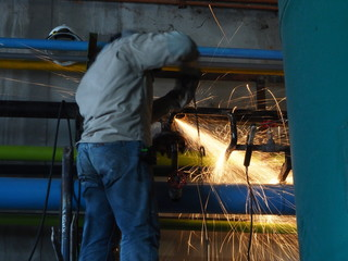 Industrial worker make a spark by grinding.